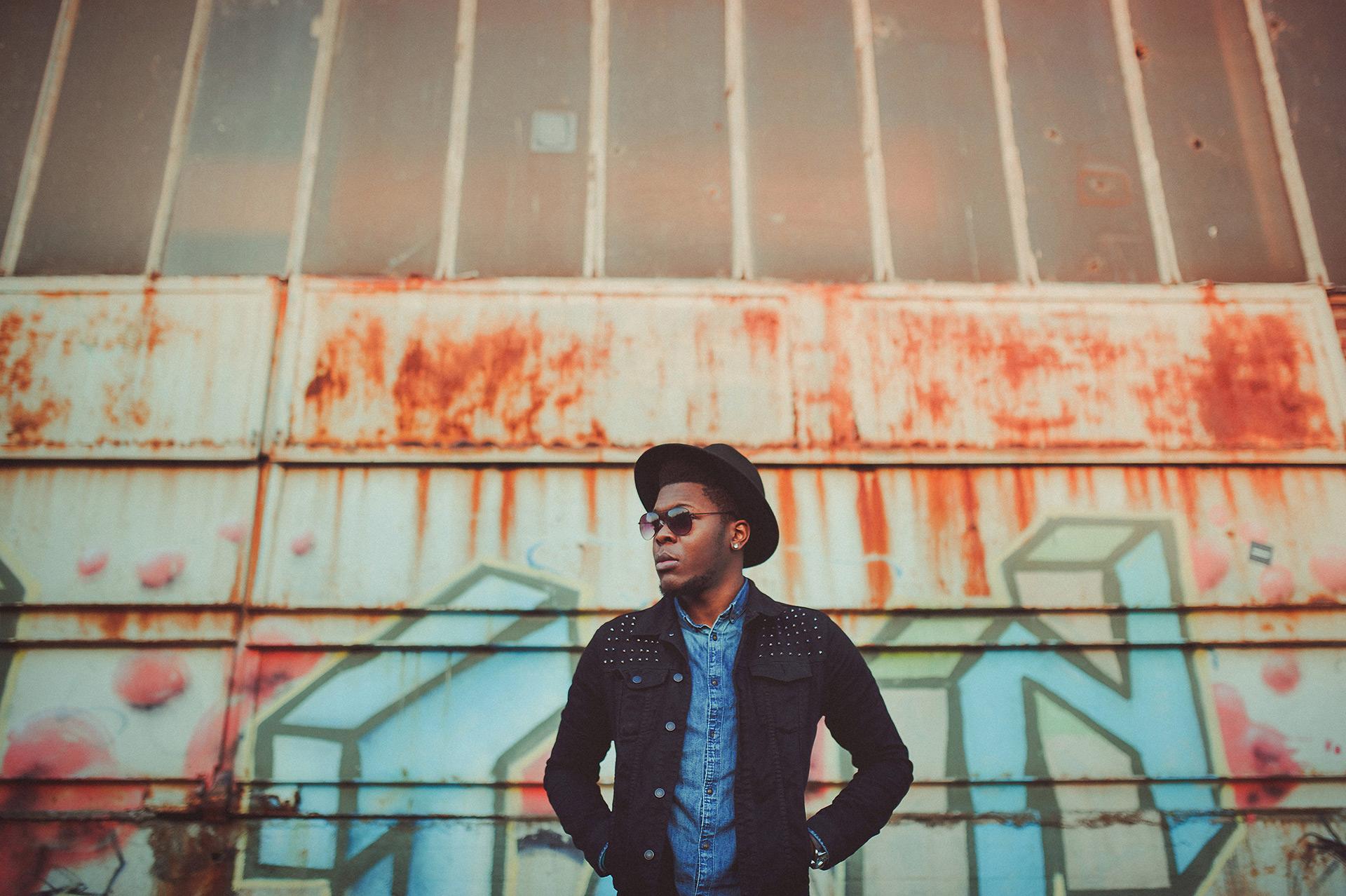 Billy mit Hut und Sonnenbrille vor einem Graffiti im Hafen